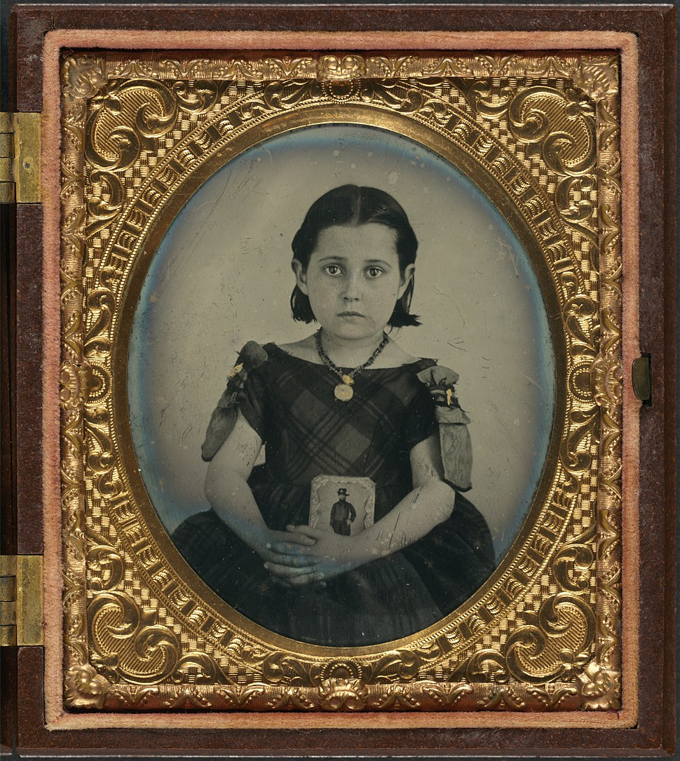 Girl in mourning dress holding framed photograph of her father