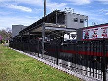 The back side of a freshly painted dark gray metal and concrete structure with red and white accents. Concession stands can be seen on the first level, seating on the second, and sky boxes on the third.