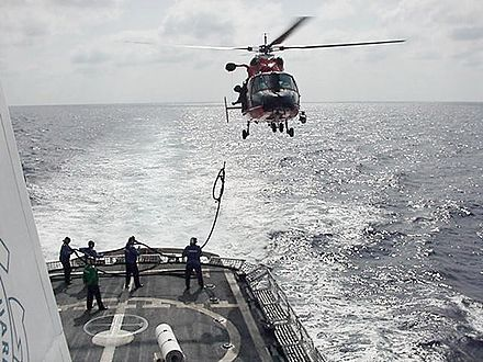 Raising a hose from ship to an HH-65. - Aerial refueling