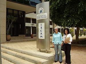 "The entrance to the IRCAM (Institut Royal de la Culture Amazighe) building in Rabat. Two women are standing in front of a large, metal plaque with the word ""IRCAM"" written on it in large letters, and the organization's logo."
