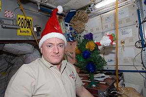English: Wearing a Santa Claus hat, NASA astro...