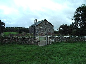A small, simple, stone church, in front of which is a stone wall.  On the far gable is a bellcote with a single bell.
