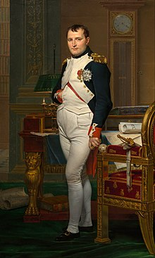 Portrait of Napoleon in his late thirties, in high-ranking white and dark blue military dress uniform. In the original image he stands amid rich 18th-century furniture laden with papers, and gazes at the viewer. His hair is Brutus style, cropped close but with a short fringe in front, and his right hand is tucked in his waistcoat.