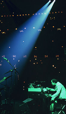 To one side of a stage, a man plays keyboards while bathed in green light