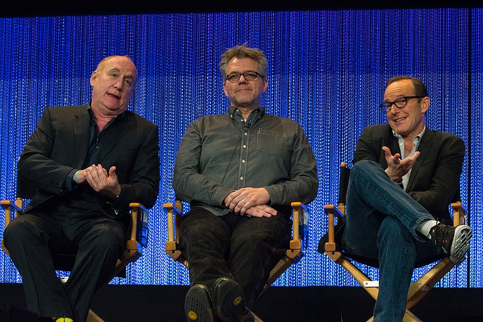 Three men sitting, facing the camera. Jeph Loeb, on the left and Jeffery Bell, middle, have their hands touching, with Clark Gregg on the right with his leg crossed.