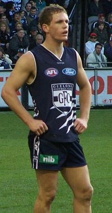 A brown-haired male athlete wearing a navy sleeveless jersey and shorts.