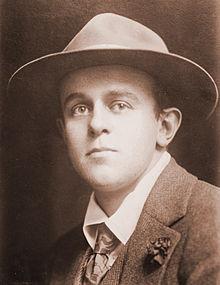 Mid-length photograph of a man of about 25 in a jacket, tie, and fedora.