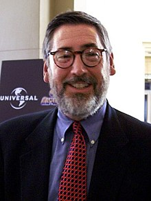 Headshot of a middle aged. Looking and smiling directly into the camera, the man wears rounded spectacles and sports a light grey beard. He wears a suit jacket, with a blue shirt and a patterned tie.