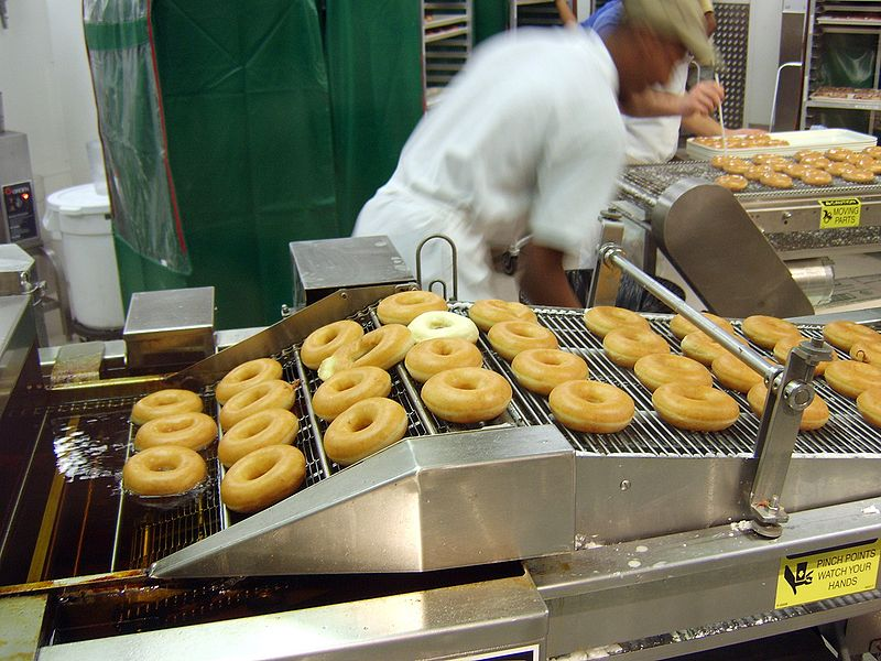 Krispy Kreme Doughnuts, original, out of the oven and on the conveyor belt about to be glazed.
