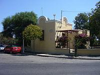 A casa de Durrell em Rodes apresenta arquitetura mediterrânea e paredes de estuque ou gesso pintadas de amarelo.  Está localizada em uma rua asfaltada, com dois carros estacionados paralelamente a ela.  A casa é cercada por várias árvores, arbustos, rosas e arbustos floridos.