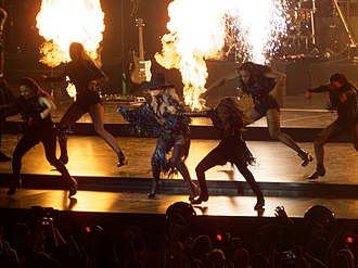 "Joanne World Tour - Gaga performing ""John Wayne"" while flamethrowers spit fire in the background"