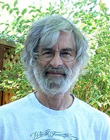 Portrait of a Caucasian man in his seventies with medium-length gray hair and a full gray beard, wearing glasses and a T-shirt.