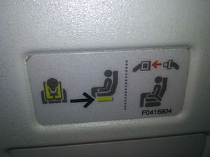 Personal flotation device - On many aircraft life vests are underneath the seats, as indicated by this sign