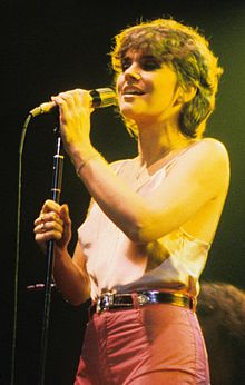 Ronstadt, in her early to mid-30s, sings in concert dressed in a camisole top and pants with medium-length hair, clutching the microphone on a stand with both hands.