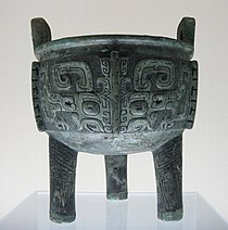 A heavily tarnished bronze bowl adorned with several carvings of squares that curl in on themselves at the bottom. It has three stubby, unadorned legs and two small, square handles coming off from the top rim.