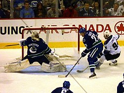 An ice hockey goaltender stretches across the net to get into position as a teammate stands to the right of the net, keeping an opposing forward away.