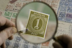 The stamp is under the examination of a magnifying glass