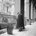 Man bij een tafeltje aan één van de zuilen in de galerij van een oud klooster wa, Bestanddeelnr 191-1350.jpg