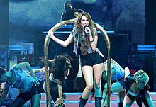 A teenage female with long, brunette hair grabs a microphone as she stands before a golden luggage cart. She is dressed in a black tank top, black hot pants, black leather boots and a blue jean vest. In the background, people ducking surround her and a DJ uses his equipment.