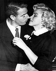 Close-up of Monroe and DiMaggio kissing; she is wearing a dark suit with a white fur-collar and he a dark suit