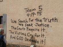 "A woman, at the left of the image, is reading a black spray paint message written on a brick wall. The message reads ""Team 5 4–19–95 We Search For the truth We Seek Justice. The Courts Require it. The Victims Cry for it. And God Demands it!"""
