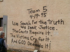 """A woman, at the left of the image, is reading a black spray paint message written on a brick wall. The message reads """"Team 5 4–19–95 We Search For the truth We Seek Justice. The Courts Require it. The Victims Cry for it. And God Demands it!"""""""