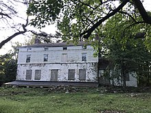 A photograph of a white abandoned house in an overgrown yard.