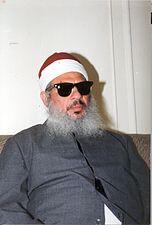 Photographie d'un homme assis sur un canapé avec une barbe blanche, portant des lunettes de soleil et un bonnet.