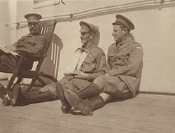 An informal group portrait of three military officers sitting on the deck of a ship.