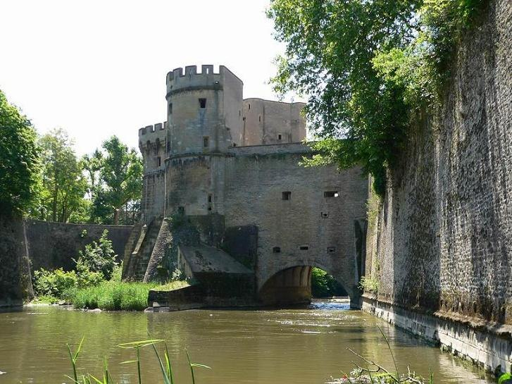 A city gate with its towers, the defensive walls, and the city ditch from the 13th century in Metz, France