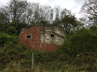 British hardened field defences of World War II - Pillbox where some of the original brick shuttering and reinforced concrete has fallen away to reveal the internal network of rebars.
