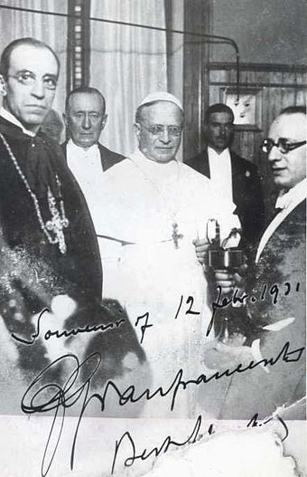Pius XI (center) with Cardinal Pacelli (front left), the radio transmission pioneer Guglielmo Marconi (back left) and others at the inauguration of Vatican Radio on 12 February 1931 PioXI et Pacelliinaugurazioneradiovaticana.jpg