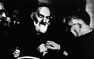 Padre Pio helped by other friars Pio of Pietrelcina.jpg