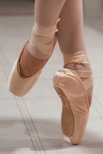 Pointe shoe - Modern pointe shoes.  The edge of the toe pad, which is inserted between the foot and toe box for cushioning, can be seen on the left foot.