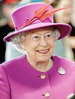 Ridetanta virino portante purpuran robon kaj egalante ĉapelon