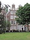 foto van Hoekhuis aan een uitstulping van het begijnhof, met een rijk gebeeldhouwde halsgevel met hoekvazen, een palmet in de volutenafdekking en ornament om de hijsbalk