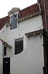 foto van Witgepleisterd laag huis met hoog zadeldak en uitbouwen. Dakkapel door daklijst snijdend met hijsbalk