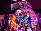 A woman wearing a neon-blue jacket with two dancers in front of a stage set
