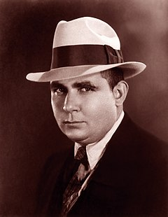 Professional photograph of Robert E. Howard wearing a hat and suit.
