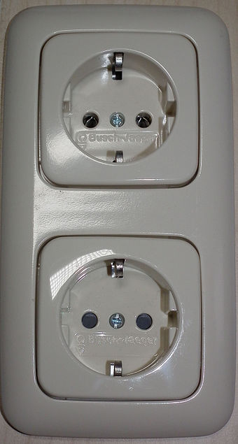 Two Schuko (CEE 7-3) socket-outlets manufactured by Busch-Jaeger Elektro GmbH, the lower has (black) protective shutters, the upper does not, revealing internal metal contacts. Schuko (CEE 7-3) socket-outlets, with and without shutters.jpg
