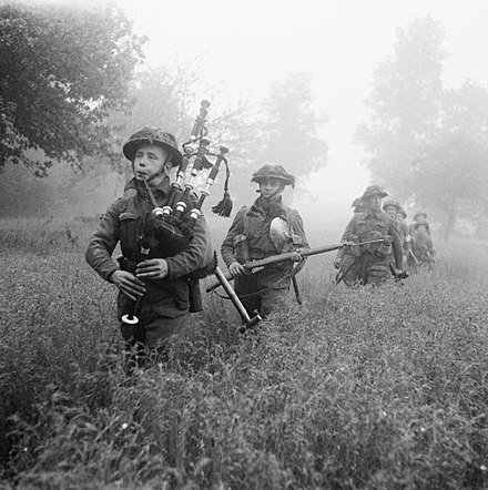 Led by their piper, men of the 7th Battalion, Seaforth Highlanders (part of the 46th (Highland) Brigade), advance during Operation Epsom on 26 June 1944 Scotishadvanceepsom.jpg