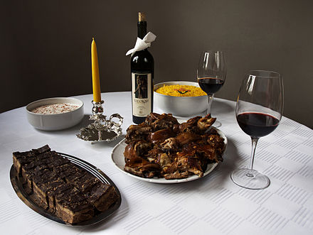 Typical Christmas table in Serbia with roasted pork, Russian salad and wine Serbian Christmas meal.jpg