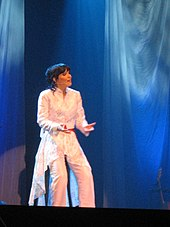 Turunen sings live onstage while seated on a stool. She is wearing a glittery white suit.