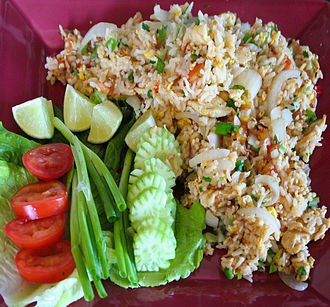 Thai fried rice - Thai fried rice, with common garnishes of cucumber, lime (for squeezing on top), tomato, and green onion served on a bed of lettuce.