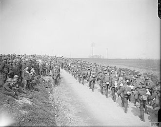 3rd Division (United Kingdom) - Men of the 1st Battalion, Royal Scots Fusiliers watching the 7th (Service) Battalion, King's Shropshire Light Infantry marching up to the outpost line, 3rd Division, 11 April 1918.