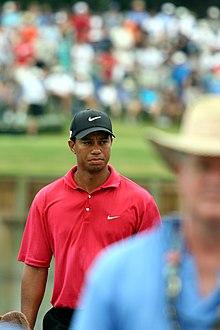Dans une image flou, un homme au polo rouge et à la casquette noire est mise en avant par sa netteté.