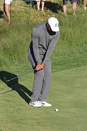 Le golfeur balance son club vers l'arrière tout en gardant les yeux sur le balle.