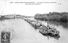 An old black-and-white photograph of a steamboat pulling many barges behind it.