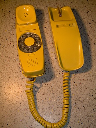 Trimline telephone - A 220 Trimline rotary desk phone, showing the innovative rotary dial with moving fingerstop