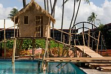 A grass and bamboo hut is sitting above a swimming pool due to bamboo stilts. A bridge made of wood is leading up from the right towards the hut. In the background is other buildings and blue, cloudy skies.